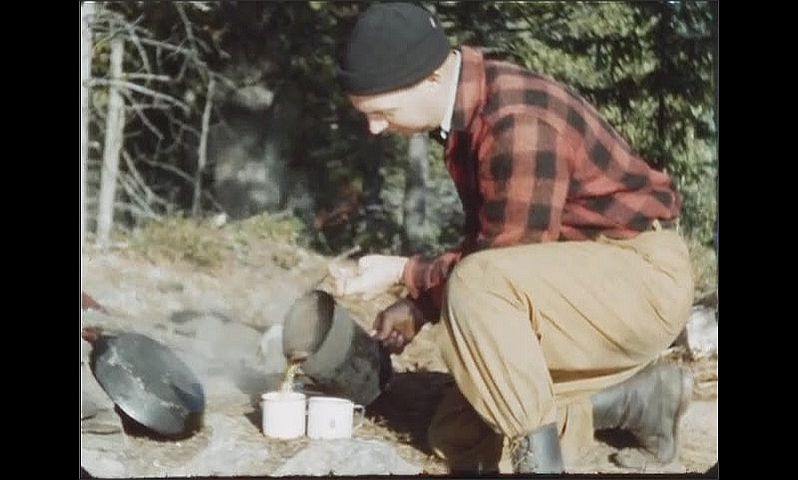 1940s: Man at campsite pours coffee from pot into mugs. Man sits, reeling fishing pole at campsite.