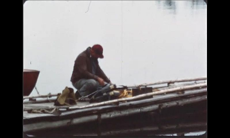 1940s: Man climbs out from under tarp being used as tent and looks at sky. Man on dock over lake, holds fishing pole.