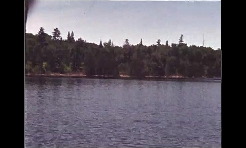 1940s: UNITED STATES: men fishing from wooden platform. Fishing gear on side of lake. Fish on line. View across lake.