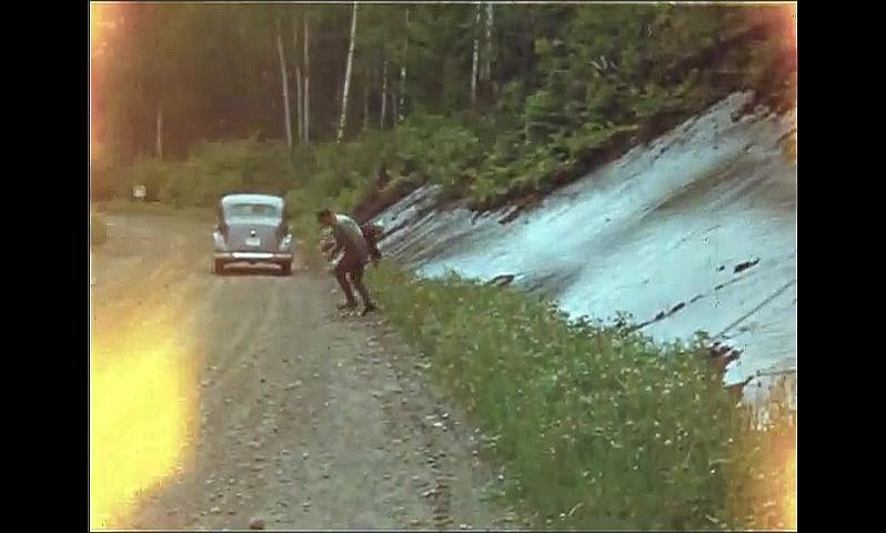 1940s: UNITED STATES: man runs up slippery slope. Jumping Caribou Creek sign.