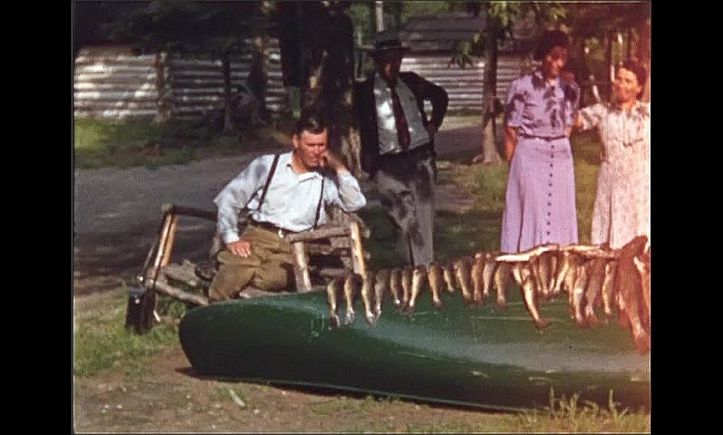 1940s: UNITED STATES: men turn over canoe on grass. Men by car. Fish hung on canoe. Ladies by boat and fish. Men play with fish in fight.