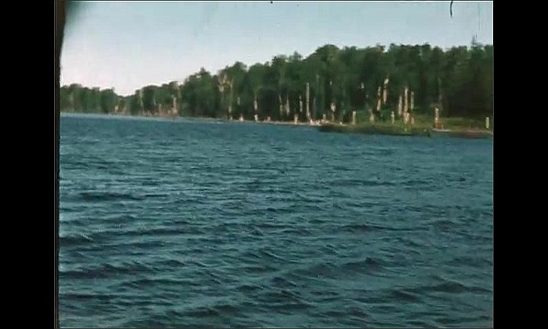1940s: UNITED STATES: view across lake from small boat. Trees by lake. Panoramic view across lake. Men in boat. Man pulls up fish on line.