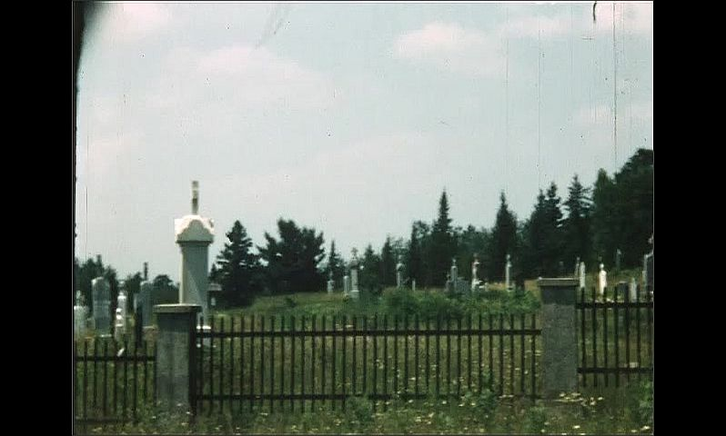 1940s: UNITED STATES: grave yard in forest. Statues on graveyard wall. Man outside cemetery. Man carries from boat.