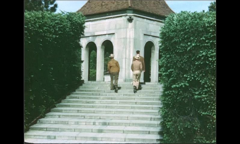 1940s: UNITED STATES: water fountain in park gardens. Ladies walk along path. Men walk up steps. Flowers in beds by path.
