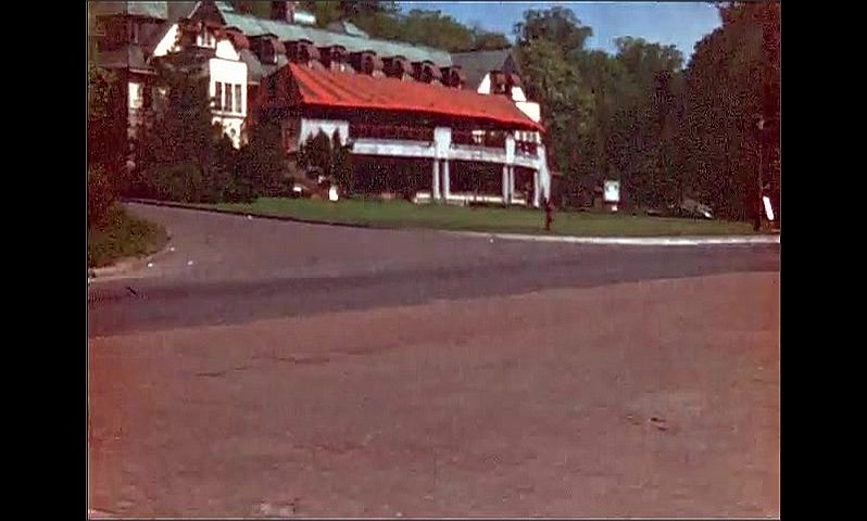 1940s: UNITED STATES: road outside building. Man with fish on line after trip. Man walks from wooden boat.