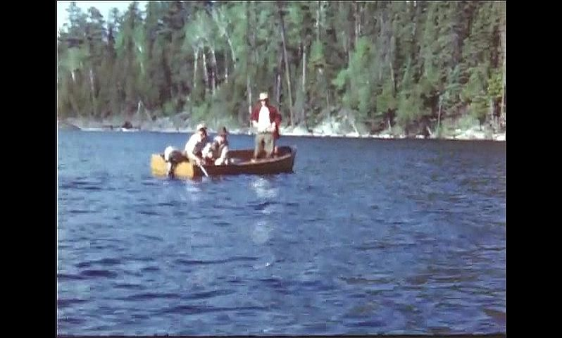 1940s: UNITED STATES: fish in frying pan on camp stove. Men in wooden boat fishing in lake. Man catches fish.
