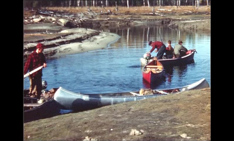 1940s: UNITED STATES: plane drives along road. Men in canoes on river shore. Man with rifle.