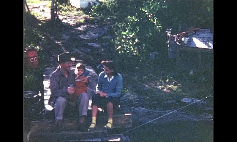 1940s: UNITED STATES: man with child on knee by lake. Lady and boy sit with man by lake. Man waves at camera.