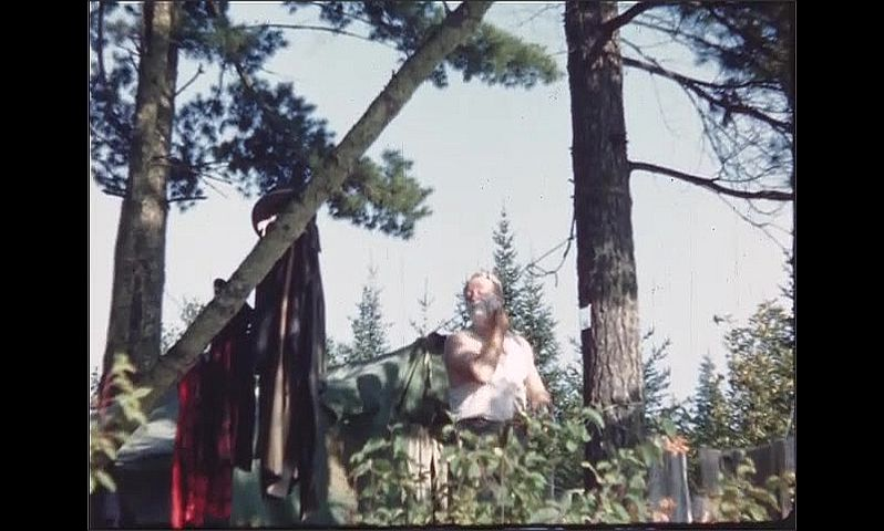1940s: UNITED STATES: man shaves in camp  by tree. Man with shaving foam on face. Men hold up fish on rope for camera.