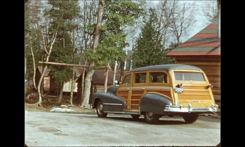 1940s: ONTARIO, CANADA: truck by log cabins. Man carries gear from shed to truck. Car drives off from cabin. Man walks on track by cabin.