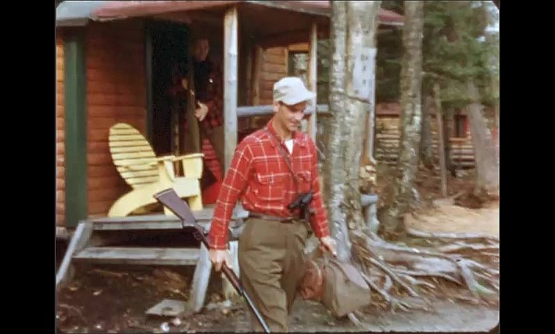 1940s: ONTARIO, CANADA: man carries fishing gear from cabin to car. Man carries gun to car. Men get ready for trip.