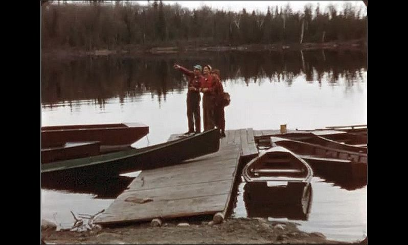 1940s: ONTARIO, CANADA: men stand by car. Men stand on jetty with binoculars.