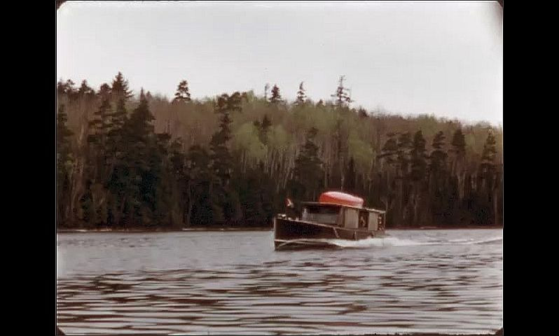 1940s: ONTARIO, CANADA: plane on water by jetty. Boat motors along water. Flag on boat. Trees on shore