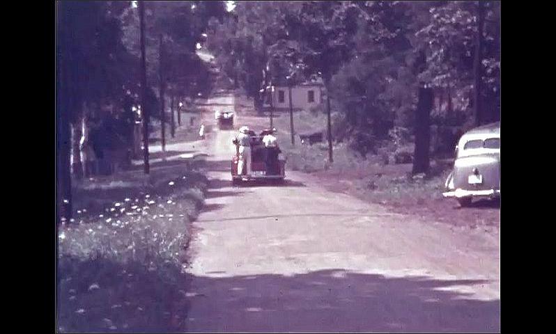 1940s: ONTARIO, CANADA: men on fire truck. Truck drives along road. Fire department volunteers run around trucks. Buildings by street.