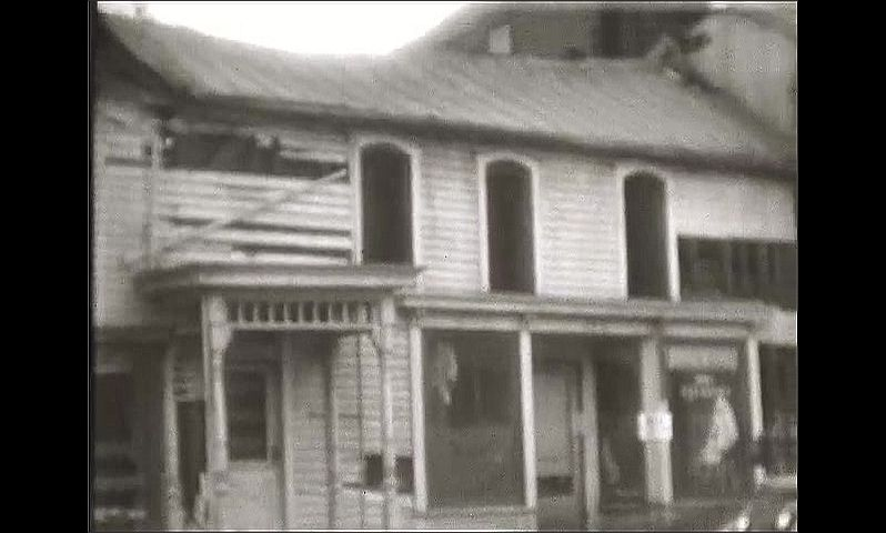1920s: UNITED STATES: shell of house after fire. Burnt building in street. Fire damage and wood.