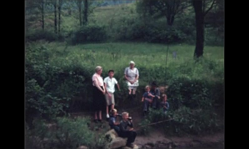 1940s: UNITED STATES: boys fishing by water. Family fish from bank of river.