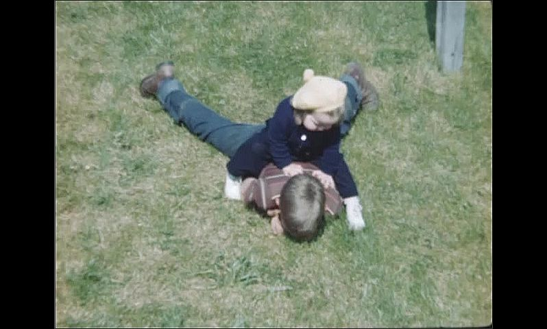 1940s: UNITED STATES: lady holds toddler's hand down steps. Toddler rides on boy's back. Boy crawls across ground
