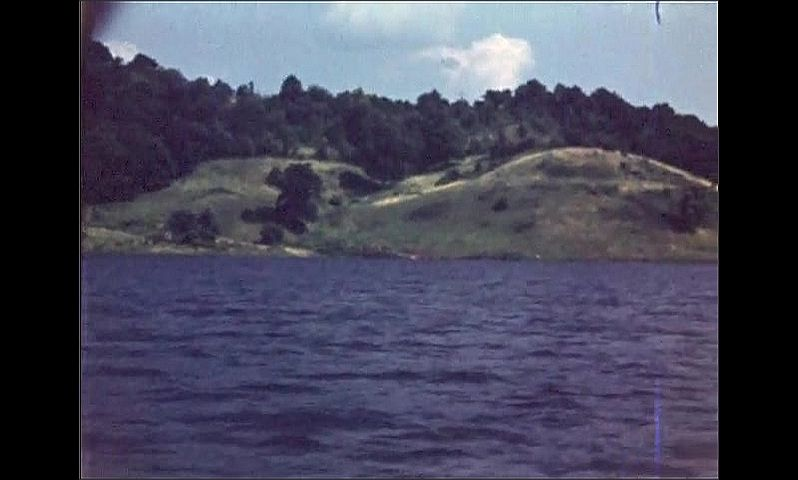 1940s: UNITED STATES: view across lake. View of water from boat. Trees by lake.