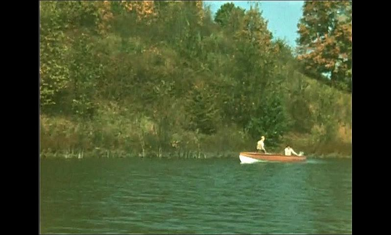 1940s: UNITED STATES: view across lake from boat. Autumn leaves on trees. Blue sky. People on boat on water.