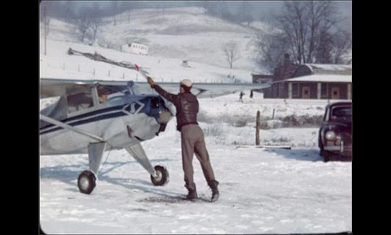 1940s: Man struggles to spin propeller on small silver plane on snowy field. He spins the propeller, jumps back, repeats several times until propeller spins on its own, he turns, skips away.