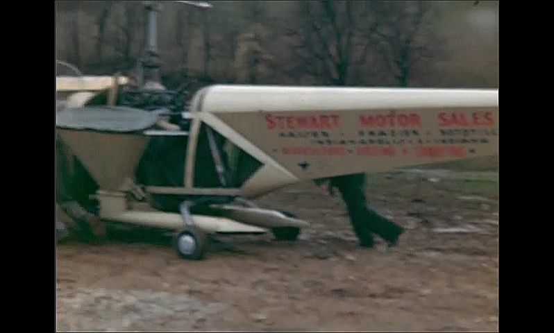 "1940s: Men push out a strange looking helicopter across a muddy field with ""Stewart Motor Sales Inc."" painted on its rear."