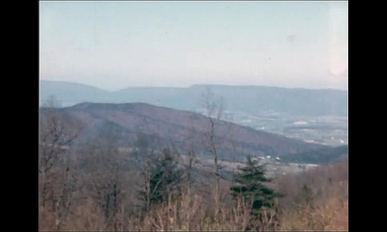 1940s: Overlooking a mountain range as the camera pans across the scenery.