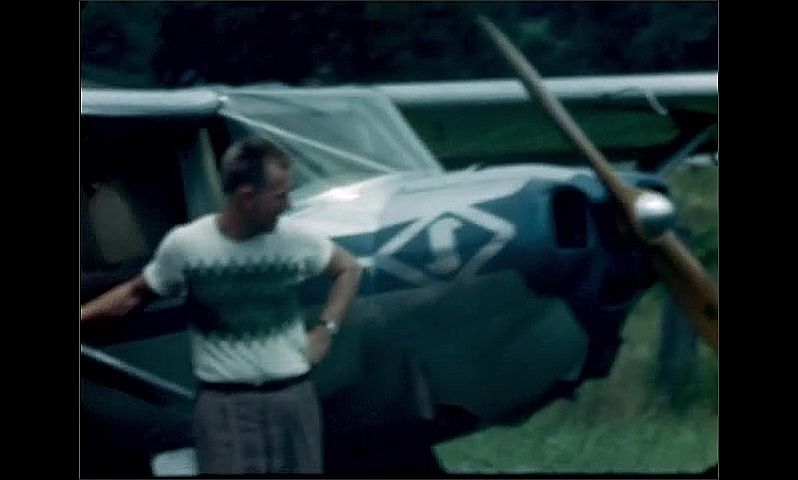 1940s: Man checks cockpit on small airplane parked in a grassy field, stands with one arm rested on the wing of the plane, looking and smiling at camera.