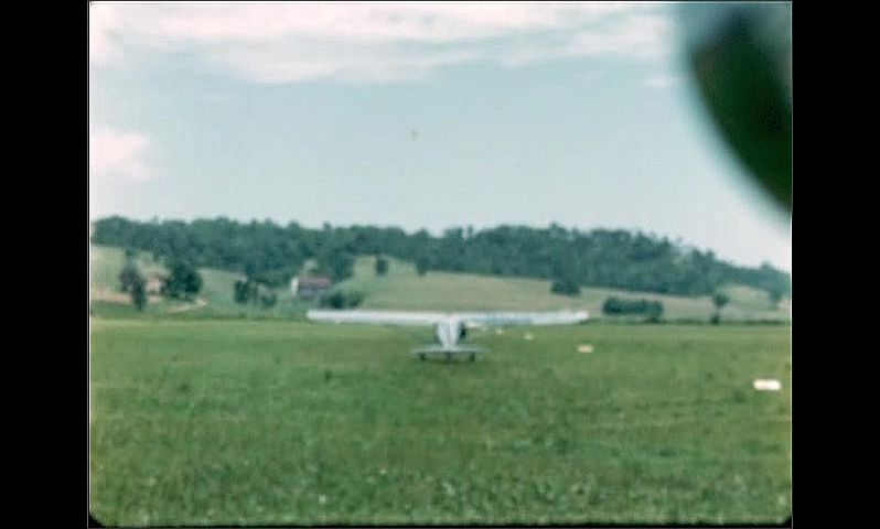 1940s: Small silver airplane rolls across grassy field towards green hills on horizon.