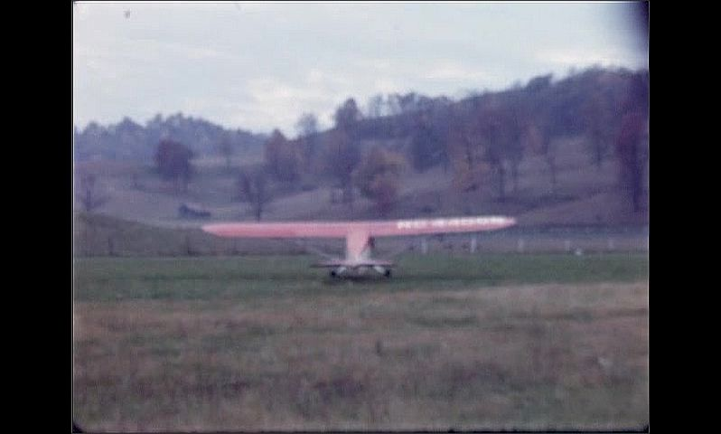 1940s: Small red and white airplane sits on grassy field, pilot in cockpit. Plane rolls down field. Field and hill behind. Plane turns on field.