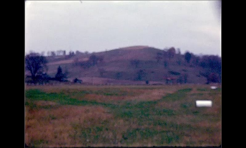 1940s: Small plane flies over green hillside, disappears behind hill. Little red plane comes in for a landing on grassy field, speeds down field.