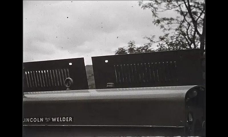 1930s: Large, metal equipment with the words Lincoln Welder on it. Man stands at end of equipment and smiles.