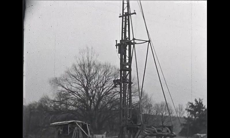 1930s: Excavation site for construction. Crane sits on site. Makeshift building. Large tower is situated on back of truck. Vehicles and equipment around site.