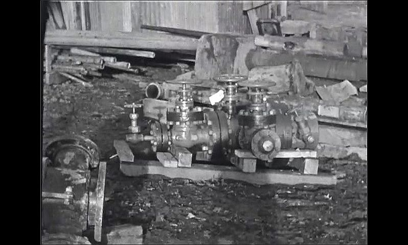 1930s: Men assist large bit on derrick as it situates itself in place in ground. Pumping equipment sits on ground waiting to be used. Long pipes sit on ground.