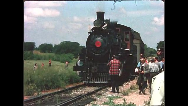 1940s: People watch as train engine reverses towards passenger cars. Front of train engine.