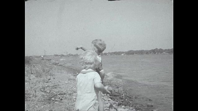 1930s: UNITED STATES: boys throw stones in sea from beach. Boy waves.