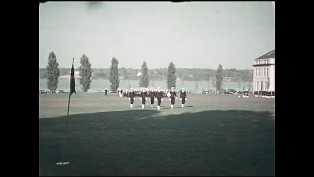 1930s: UNITED STATES: smoke from building. Man carries flag. Men in uniform by building