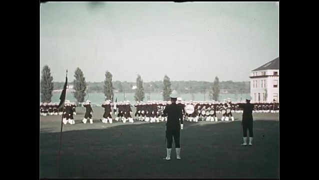 1930s: UNITED STATES: men in uniform on grass. Men practice drill. Marching band on field.