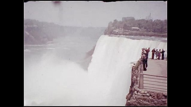 1930s: UNITED STATES: boys wave at camera. Lady in suit holds flowers. Visit to Niagara Falls.