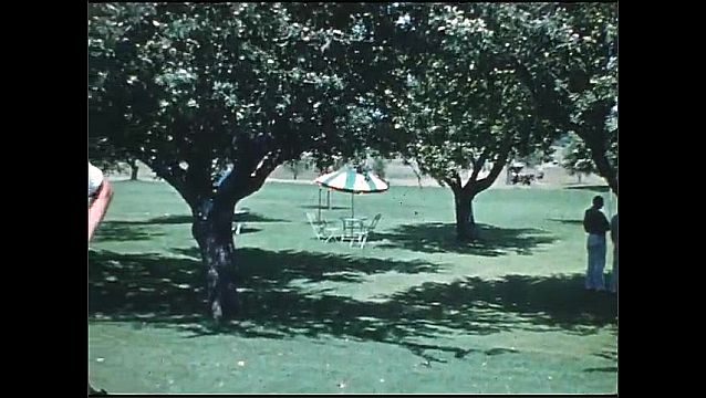 1930s: Golf course. Men stand in shade of trees, man putts, man walks by with golf bag, two men hold golf clubs and smile, one takes of cap and sucks in stomach.