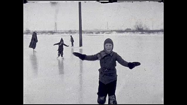 1930s: Little boy sits on frozen pond, rolls over. Woman in fur coat skates out on pond with little boy, lets go, skates off, boy falls. Boy struggles to skate, falls on stomach with smile.