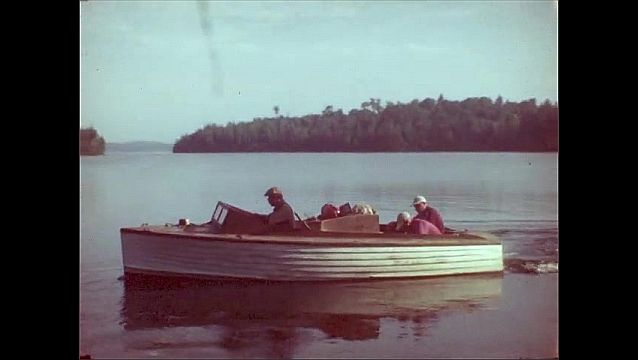 1940s: Men walk from cabins in woods. Men gather on docks and board fishing boats. Men drive motorboat into lake. Men drive boat toward island in lake.