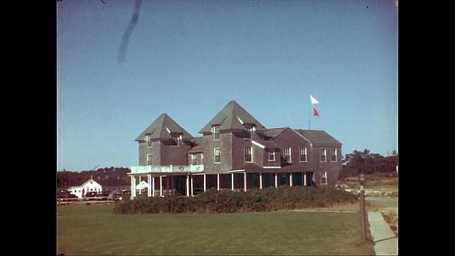 1940s: Man and boy sit on chairs at lakeside beach. Flags flutter on roof of large wooden building near lake. Man walks from large buildings toward parking lot.