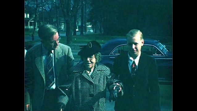 1940s: Men help elderly woman walk from car up sidewalk.