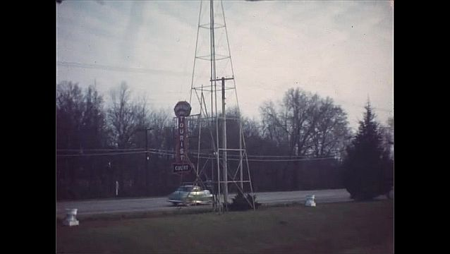 1940s: Neon sign hangs from pole near roadside. Hotel office building. Windmill turns near buildings. Large white university buildings on campus.