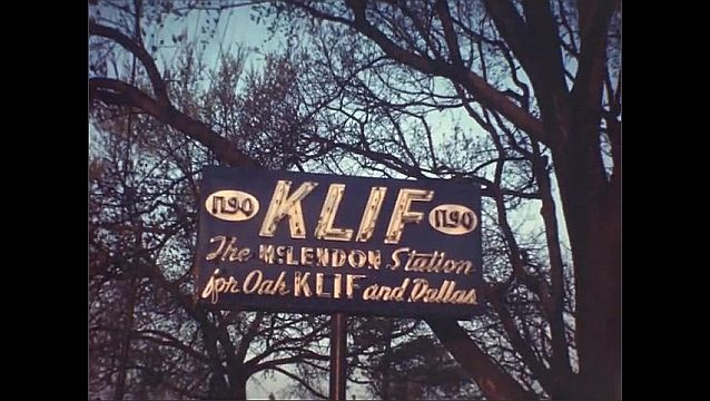 1940s: Aerial view of lake and small town. Cars drive past trees and lake. Neon sign for KLIF 1190. Lake near town. Brick archway leads to large skyscraper building.