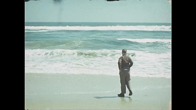 1940s: UNITED STATES: boys stand by waves on shore. Boy throws stone in sea. Boy by waves.