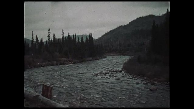 1930s: UNITED STATES: Visit to Laurentian Mountains and River Pikauba. Autumn tree colours in mountains. View of river. Car on track by river.