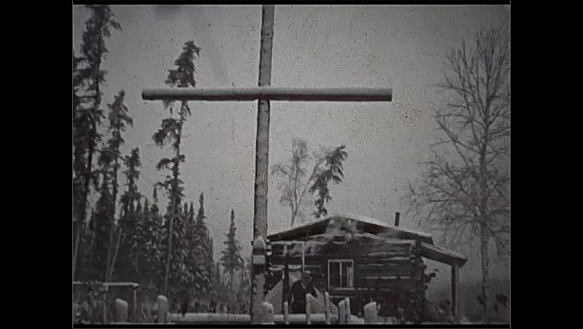 1930s: UNITED STATES: Serpent River camp. October 9th 1937. Men smoke by cabin. 13th October 1937. Cross by camp. Snow in camp.