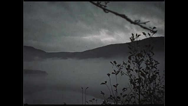 1930s: UNITED STATES: men by camp fire in snow. Mist over river. Mountains and woods by lake.