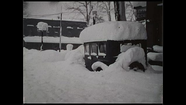 1930s: UNITED STATES: snow around house and garden. Man walks through snow in street. Car covered in snow. Lady and boy walk in snow